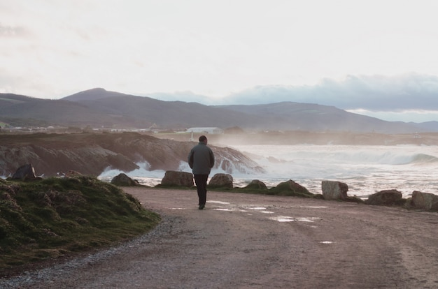 Man walking along the coast on a rainy day with big waves.