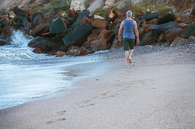 ビーチに沿って歩く男