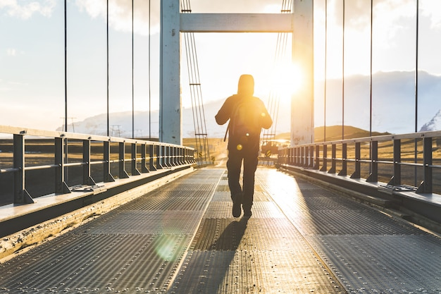 Man walking on bridge at sunset, adventure and wanderlust