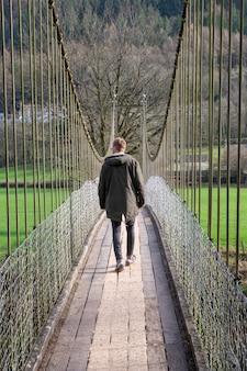 A man walking over a bridge