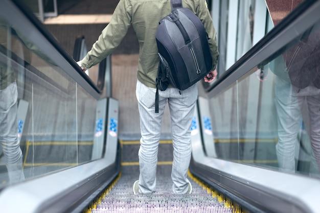 A man walking down the steel escalator in the subway