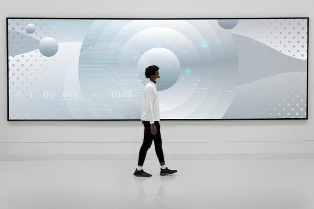 Uomo che cammina davanti a un grande cartellone