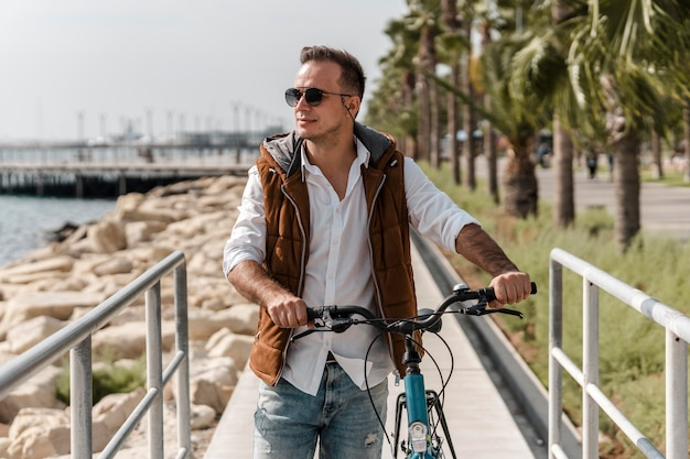 Uomo che cammina accanto alla sua bici all'aperto