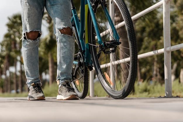 Uomo che cammina accanto alla sua bici