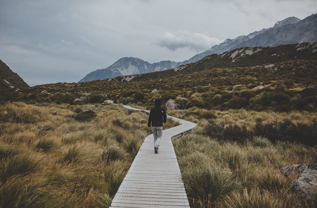 Man walking in hooker valley with a view of mount cook in new zealand