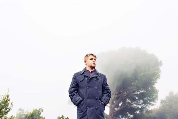 霧の森を歩く男