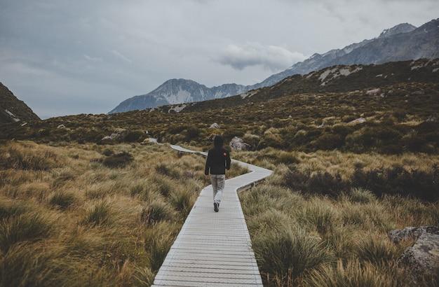 뉴질랜드에서 마운트 쿡을 볼 수있는 후커 밸리를 걷는 남자 무료 사진