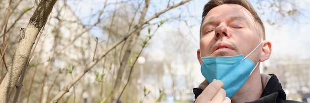 公園を歩いて、顔から保護マスクを脱いでいる男