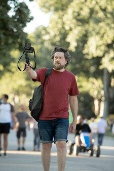 夏に自分を撮影しながら公園を歩いている男