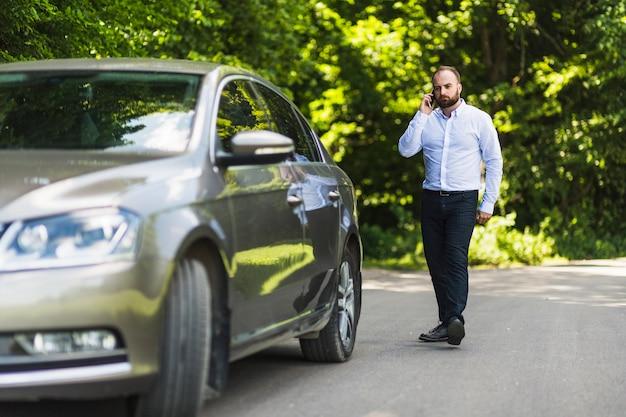 핸드폰에 얘기하는 차 근처 산책하는 남자