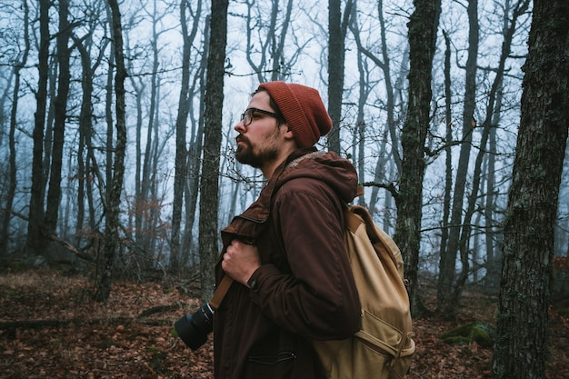 Человек идет по темной тропе через жуткий лес. хипстер с рюкзаком за спиной отправляется в путешествие