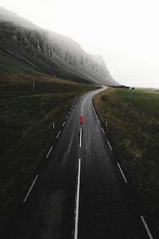 アイスランドの道路を歩いている男