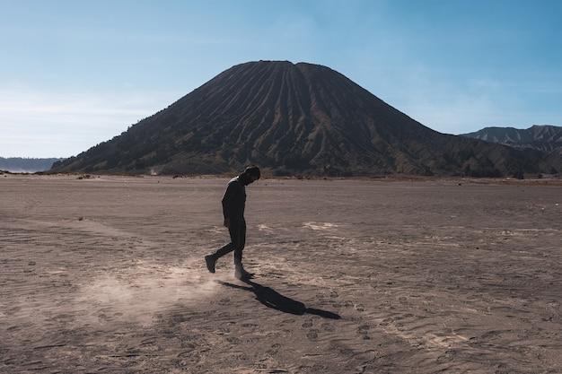 Bromo tengger semeru 국립 공원의 batok 화산 근처에서 먼지와 함께 사막을 걷는 남자
