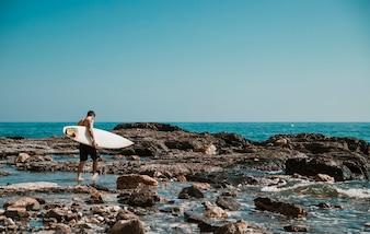 Man walking on sea shore with surfboard