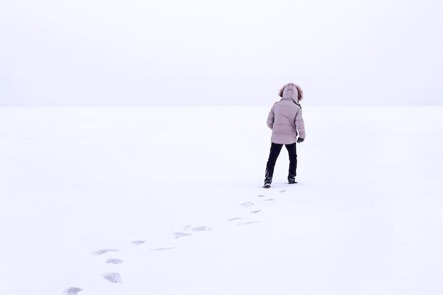 눈 위를 걷는 남자, 눈 위의 발자국, 뒤에. 추운 시베리아 겨울. 러시아. 후드와 함께 겨울 재킷에 남자입니다. 흰색 다운 재킷