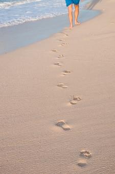 발자국을 떠나 해변을 걷고 남자