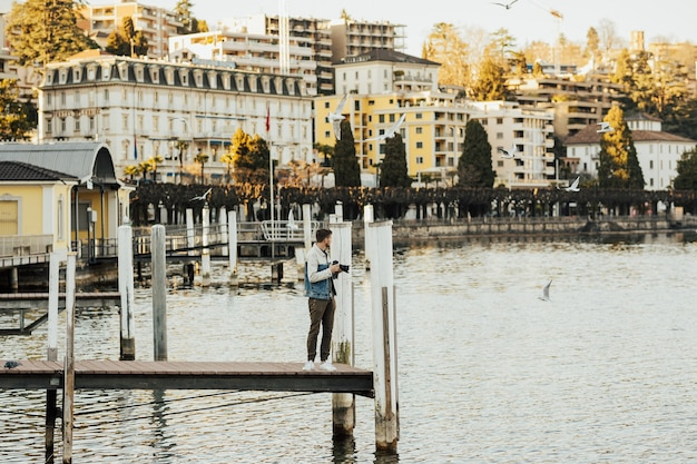 桟橋を歩いて、カメラのカモメと一緒に写真を撮る男。