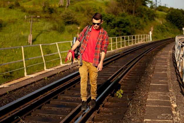 電車のレールの上を歩く男
