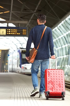 旅行のバッグと駅のプラットフォームを歩いている男