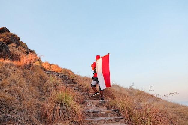 A man walking to the peak with the carrying indonesian flag