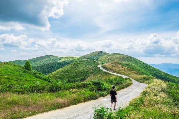 Человек идет кривой путь дороги на горном холме