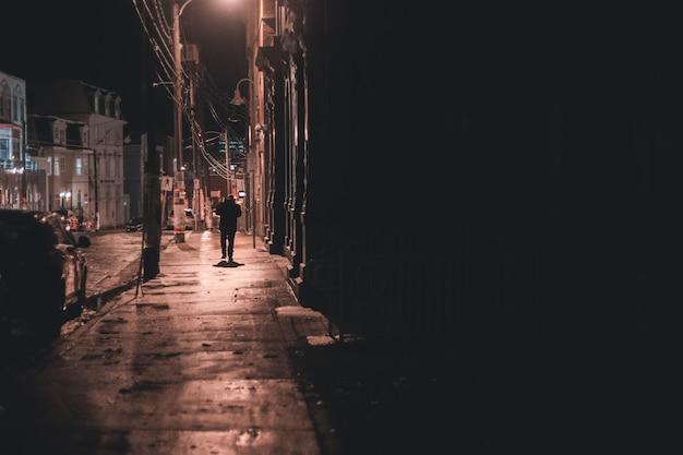 Uomo che cammina sul marciapiede durante la notte