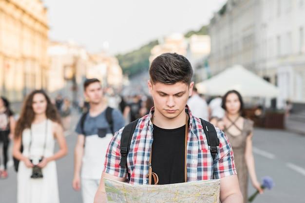 Uomo che cammina sulla strada con la mappa
