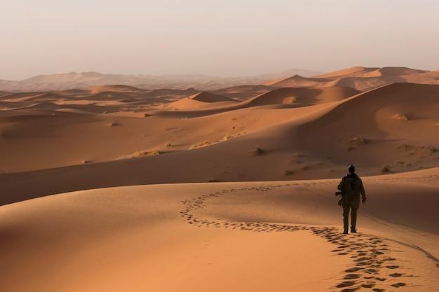 砂漠の砂丘を歩く男
