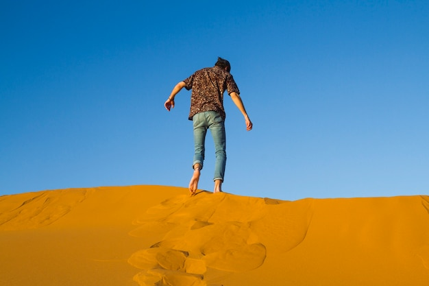 Man walking on top of dune in desert