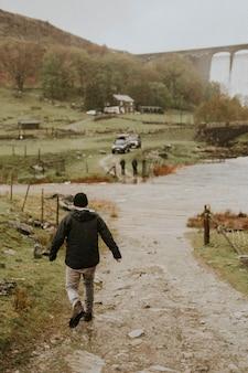 ダム構造の田舎で彼の友人に向かって歩いている男