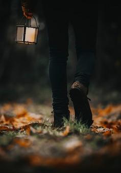 숲에서 등불을 들고 걷는 남자