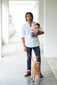Man walking with baby and his pet
