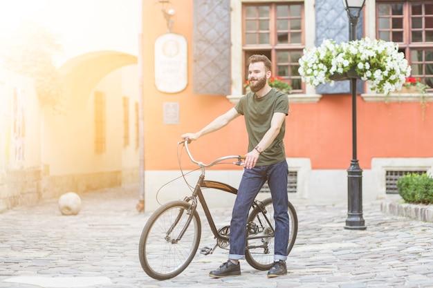 Человек, идущий со своим велосипедом на каменном тротуаре