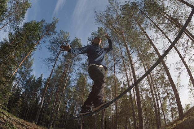 A man walks along a slackline in a picturesque pine forest. low angle. wide angle