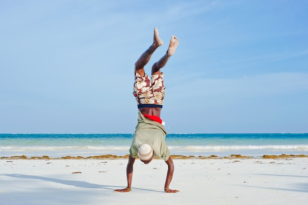 Man walks on his hands. diani beach