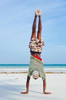 Man walks on his hands. diani beach