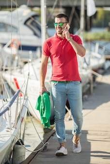 A man walks near the boat and speaks on the phone.