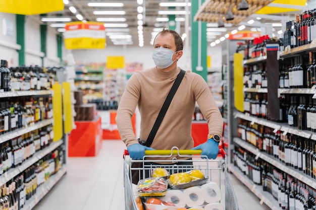 Man walks in supermarket with shopping trolley with goods, wears medical mask and rubber gloves, food running out because of coronavirus
