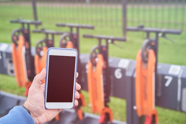 남자는 전기 스쿠터 대여를 위해 앱 qr 코드를 사용하고 케이블 잠금 장치를 잠금 해제하려고합니다.