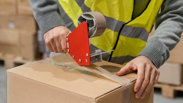 Uomo in magazzino che lavora con i pacchetti