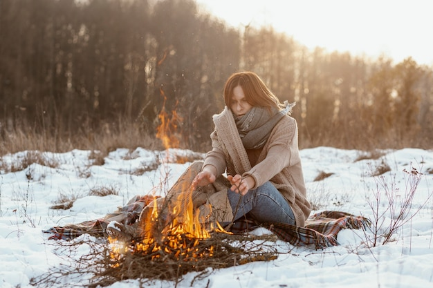 Uomo in fase di riscaldamento accanto a un falò in inverno