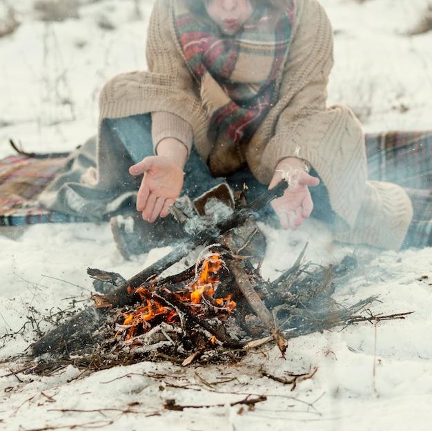 Мужчина греется у костра зимой