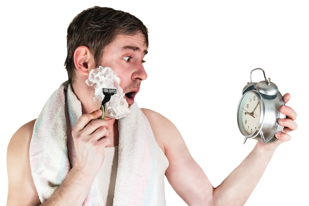 The man was late for work in the morning. he holds a classic alarm clock in his hands and shaves a litzo in a hurry. funny facial expression. isolated white background.
