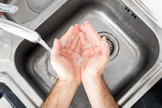 남자는 금속 싱크대에 비누와 물로 손을 씻는다