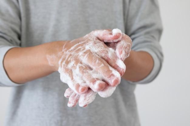 Covid-19コロナウイルス防止の概念のための石鹸で手を洗う人