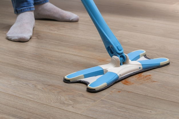 A man washes the floors with a mop in the room. under the bed. cleaning.