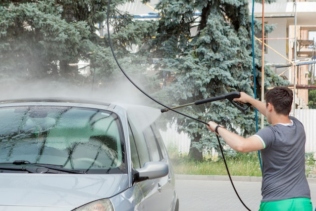 A man washes his car in a self-service sink in the summer outdoors.