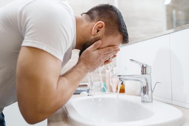 Мужчина моет лицо в ванной, рутинная утренняя гигиена.