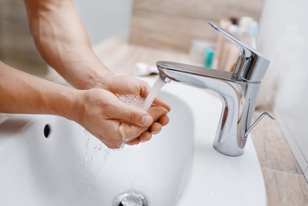 男はいつもの朝の衛生状態で、トイレで顔を洗います。
