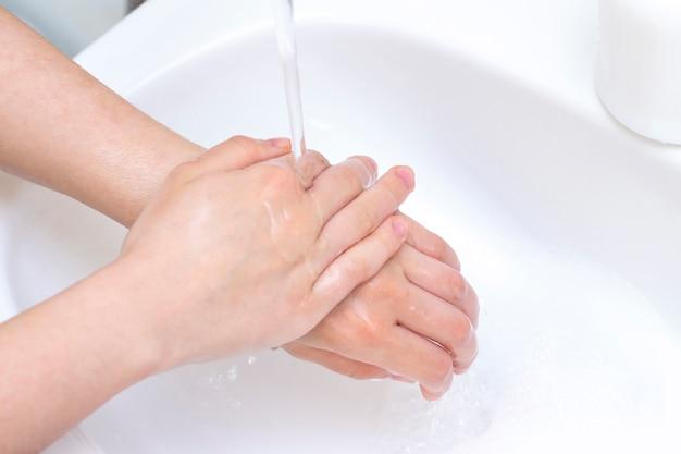 男は手を洗います。抗菌石鹸の泡で手。細菌、コロナウイルスに対する保護。手指衛生。水で手を洗ってください。多くの手